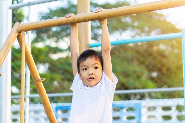 Glücklicher asiatischer kinderjunge, der von einer stahlstange am spielplatz spielt und hängt. Premium Fotos