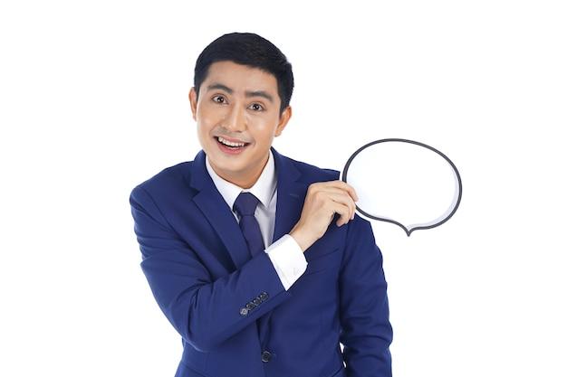 Glücklicher asiatischer lächelnder junger geschäftsmann, der blasensprache hält, lokalisiert auf weißem hintergrund Premium Fotos