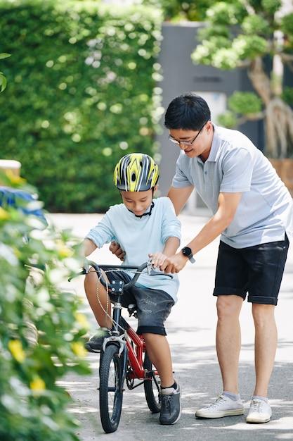 Glücklicher asiatischer mann, der jugendlichen sohn im helmfahrrad im haushinterhof lehrt Premium Fotos
