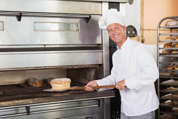 Glücklicher bäcker, der frisches laib herausnimmt Premium Fotos