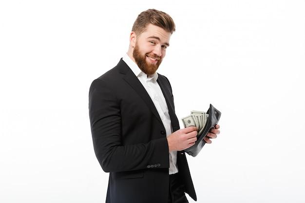 Glücklicher bärtiger geschäftsmann, der geldbeutel mit geld hält Kostenlose Fotos