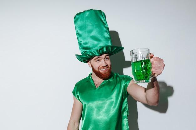 Glücklicher bärtiger mann im grünen kostüm, der tasse hält Kostenlose Fotos