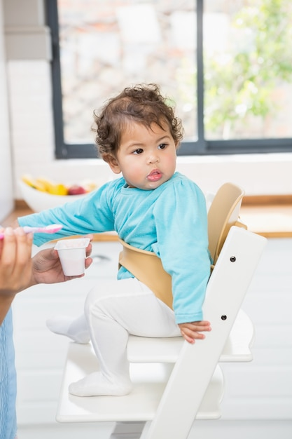 Glücklicher brunette, der ihr baby in der küche einzieht Premium Fotos