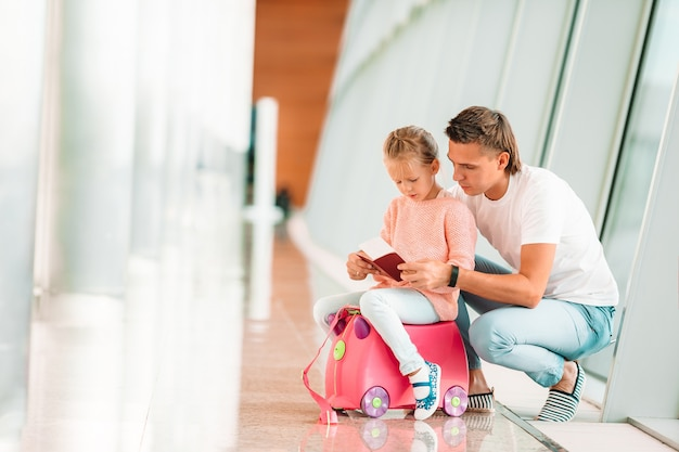 Glücklicher dada und kleines mädchen mit bordkarte am flughafen Premium Fotos
