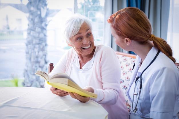 Glücklicher doktor und patient, die ein buch liest Premium Fotos