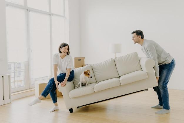 Glücklicher ehemann und ehefrau setzen sofa in wohnzimmer, richten ihr erstes zuhause ein, helfen sich gegenseitig bei der renovierung Premium Fotos