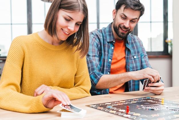 Glücklicher ehemann und frau, die das visitenkartenspiel spielt Kostenlose Fotos