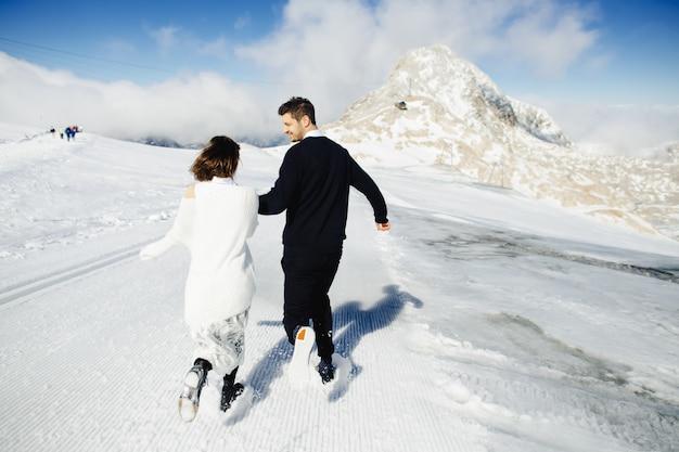 Glücklicher ehemann und frau laufen irgendwo im schnee Kostenlose Fotos