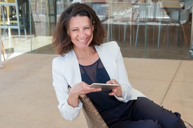 Glücklicher eleganter weiblicher tourist, der tablette verwendet Kostenlose Fotos