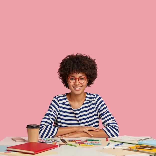 Glücklicher erfolgreicher designer trägt matrosenpullover, hält hände auf dem tisch, verwendet buntstifte zum zeichnen von meisterwerken, lächelt breit, genießt kaffee zum mitnehmen, isoliert über rosa wand mit freiem platz für text Kostenlose Fotos
