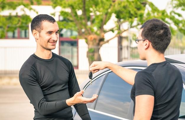 Glücklicher erfüllter junger mann, der autoschlüssel nach gebrauchtverkauf empfängt Premium Fotos