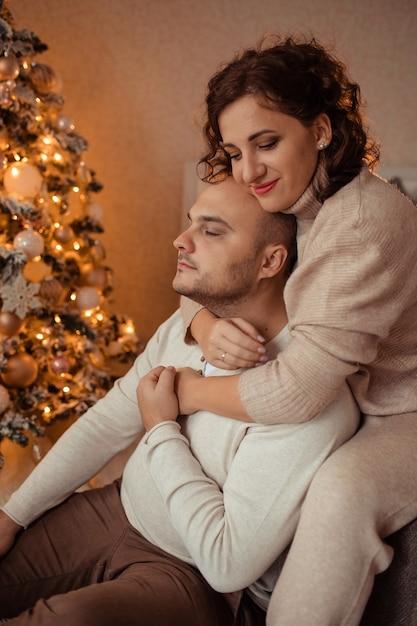 Glücklicher familienmann und ehefrau umarmen sich zu hause auf dem bett in der nähe des weihnachtsbaumes. Premium Fotos