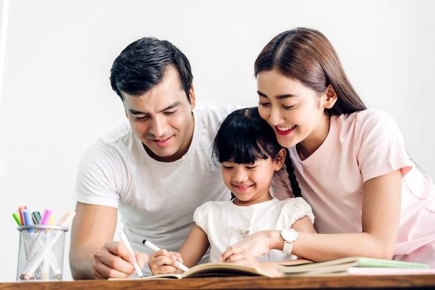 Glücklicher familienvater und mutter mit tochter, die im notizbuch mit bleistift lernen und schreiben, hausaufgaben zu hause machen. bildungskonzept Premium Fotos
