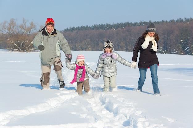 Glücklicher familienwinterspaß draußen. lächelnde eltern mit den kindern, die mit schnee auf winterferien spielen Premium Fotos