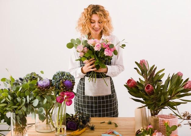 Glücklicher florist des mittleren schusses, der blumen betrachtet Kostenlose Fotos