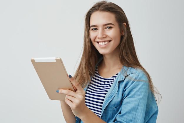 Glücklicher freundlicher herrlicher weiblicher assistent, der breites digitales tablett breit lächelnd, freudig posierend, zufrieden, wie einfach zeichnen mit gadget posiert Kostenlose Fotos
