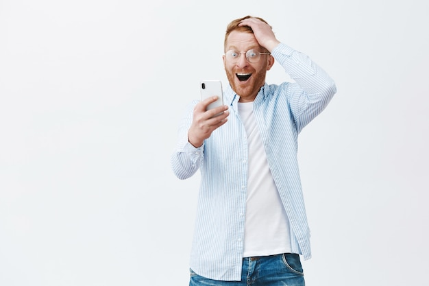 Glücklicher fröhlicher europäer in brille und hemd, haarschnitt berührend, während er erfreut und erstaunt auf den smartphonebildschirm starrt Kostenlose Fotos