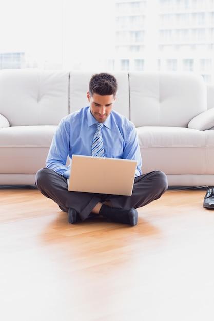 Glücklicher geschäftsmann, der auf boden unter verwendung seines laptops sitzt Premium Fotos