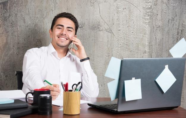 Glücklicher geschäftsmann, der über geschäft spricht und notizen am schreibtisch macht. Kostenlose Fotos