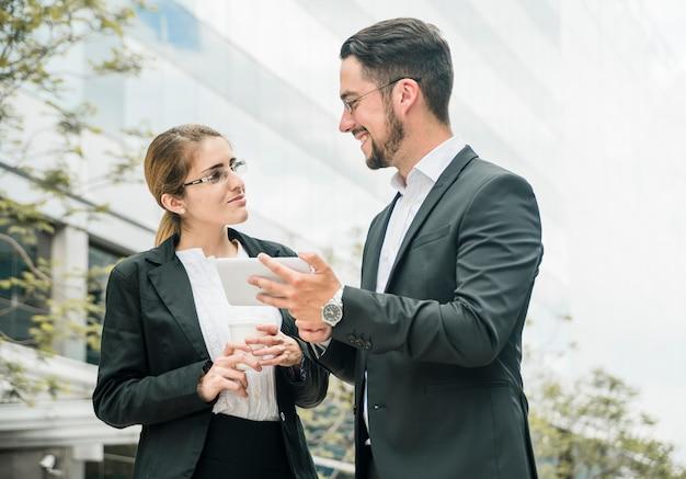 Glücklicher geschäftsmann und geschäftsfrau, die außerhalb des büros steht, das einander betrachtet Kostenlose Fotos