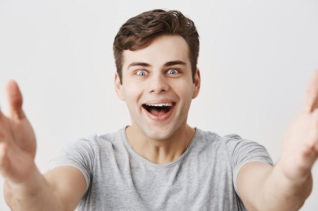 Glücklicher gutaussehender europäer lächelt glücklich, als er angenehme worte von den eltern erhält, weiße, perfekte zähne demonstriert und seine arme zur kamera ausstreckt. junger männlicher student freut sich über erfolgreichen tag Kostenlose Fotos