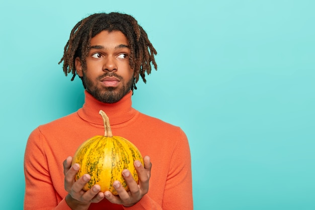 Glücklicher halloween-tag. der nachdenkliche bärtige mann hält einen kleinen kürbis in der hand und denkt darüber nach, tolle herbstferien zu organisieren, gekleidet in einen orangefarbenen rollkragenpullover Kostenlose Fotos