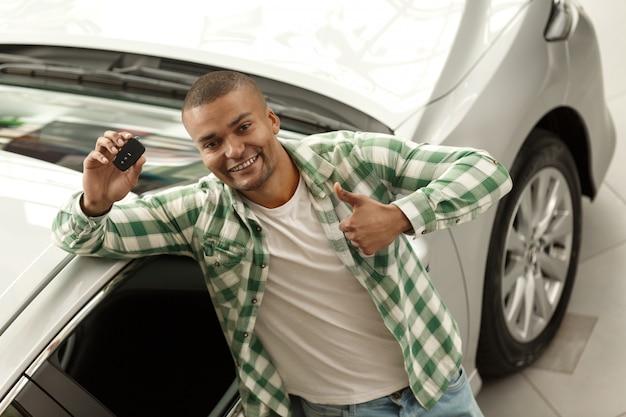 Glücklicher hübscher afrikanischer mann, der die daumen hochhalten autoschlüssel an der verkaufsstelle zeigt. Premium Fotos