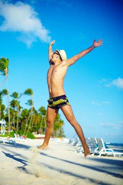 Glücklicher hübscher mann mit muskeln im sunhat auf dem strand, der hinter blauen himmel hinter blauen himmel springt Kostenlose Fotos