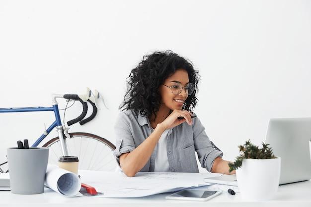 Glücklicher hübscher weiblicher ingenieur, der über büroinnenraum sitzt und dokumente hat Kostenlose Fotos