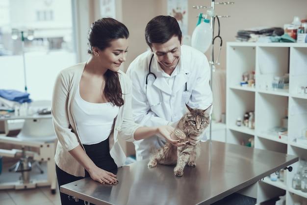 Glücklicher inhaber gibt der katzen-frau nahrung, die blechdose hält Premium Fotos
