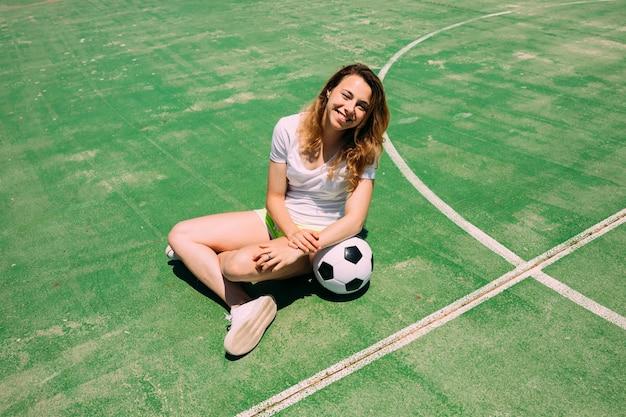 Glücklicher jugendlicher mit ball auf fußballplatz Kostenlose Fotos