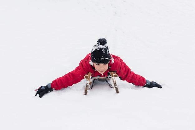 Glücklicher junge, der auf schlitten in der schneebedeckten landschaft sledging Kostenlose Fotos