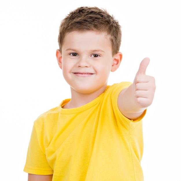 Glücklicher junge, der daumen hoch geste zeigt. auf weiß aufgesetzt Kostenlose Fotos