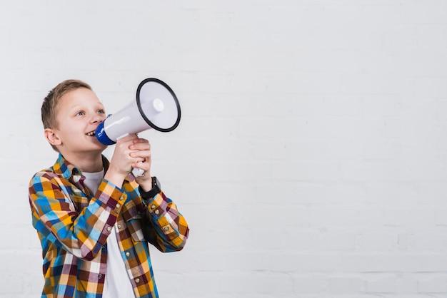 Glücklicher junge, der durch das megaphon steht gegen weiße wand schreit Kostenlose Fotos