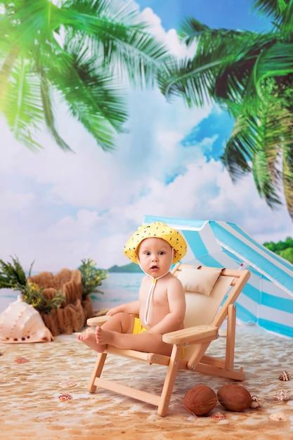 Glücklicher junge, der sich auf einem hölzernen liegestuhl an einem sandstrand am meer unter einem sonnenschirm sonnen Premium Fotos