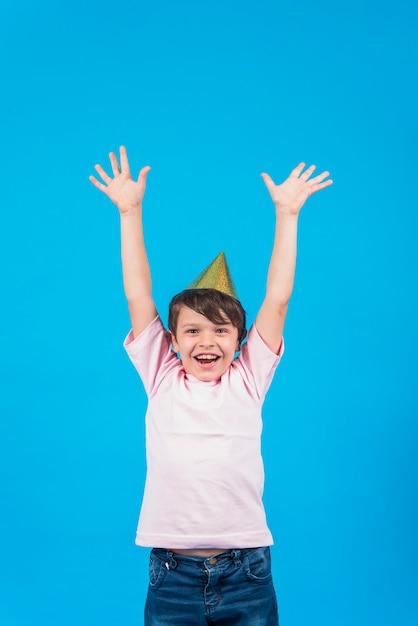 Glücklicher junge im partyhut mit dem arm hob gegen blauen hintergrund an Kostenlose Fotos