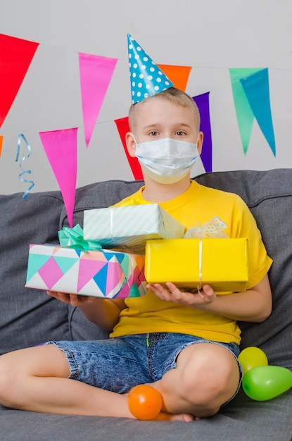 Glücklicher junge in der gesichtsmaske der medizin mit geschenken in der hand feiert geburtstag Premium Fotos