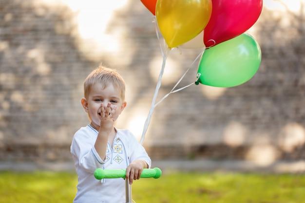 Glücklicher junge mit buntem ballon. Premium Fotos