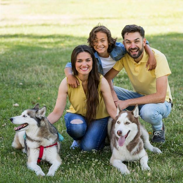 Glücklicher junge mit hunden und eltern, die zusammen am park aufwerfen Premium Fotos