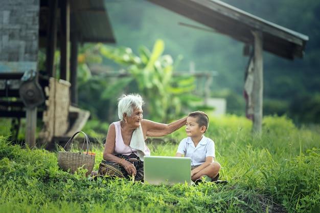 Glücklicher junge und großmutter, die draußen einen laptop verwendet Premium Fotos