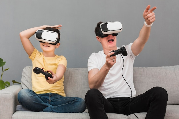 Glücklicher junge und mann, die videospiele unter verwendung des virtual-reality-headsets spielen Kostenlose Fotos