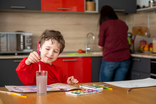 Glücklicher junge zeichnet malerei auf küche mit mutter Premium Fotos