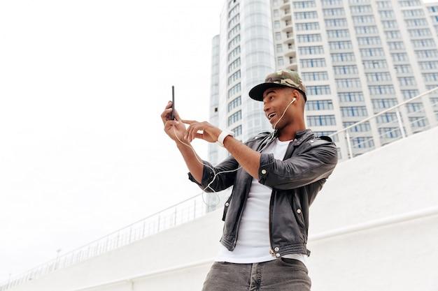 Glücklicher junger afrikanischer mann, der draußen geht Kostenlose Fotos