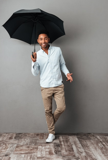 Glücklicher junger afrikanischer mann, der mit offenem regenschirm steht Kostenlose Fotos