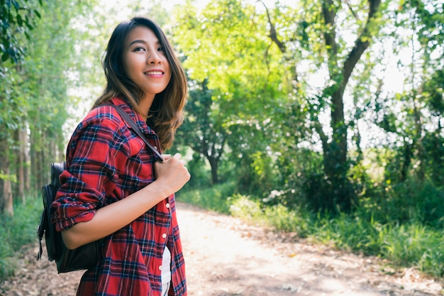 Glücklicher junger asiatinreisender mit rucksack gehend in wald. Kostenlose Fotos