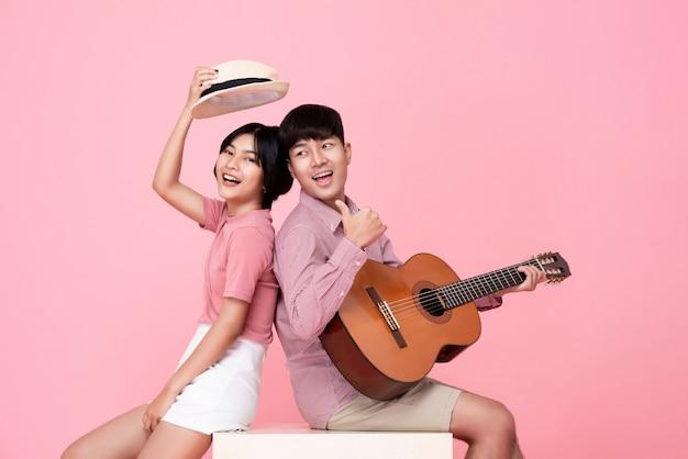 Glücklicher junger asiatischer mann, der gitarre spielt und mit seiner freundin singt Premium Fotos