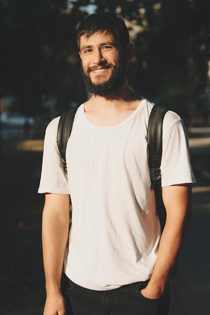 Glücklicher junger bärtiger mann im weißen t-shirt, der rucksack trägt und an der kamera lächelt, die im sonnenlicht steht Premium Fotos