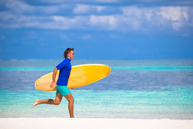 Glücklicher junger brandungsmann, der am strand mit einem surfbrett läuft Premium Fotos