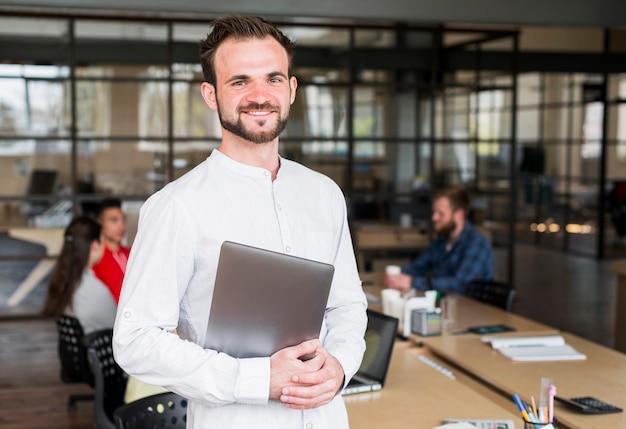 Glücklicher junger geschäftsmann, der die kamera hält laptop im büro betrachtet Kostenlose Fotos