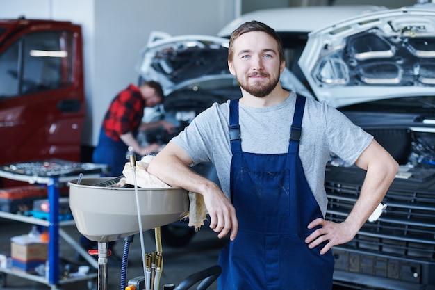 Glücklicher junger handwerker im blauen overall, der sie in der werkstatt ansieht Premium Fotos